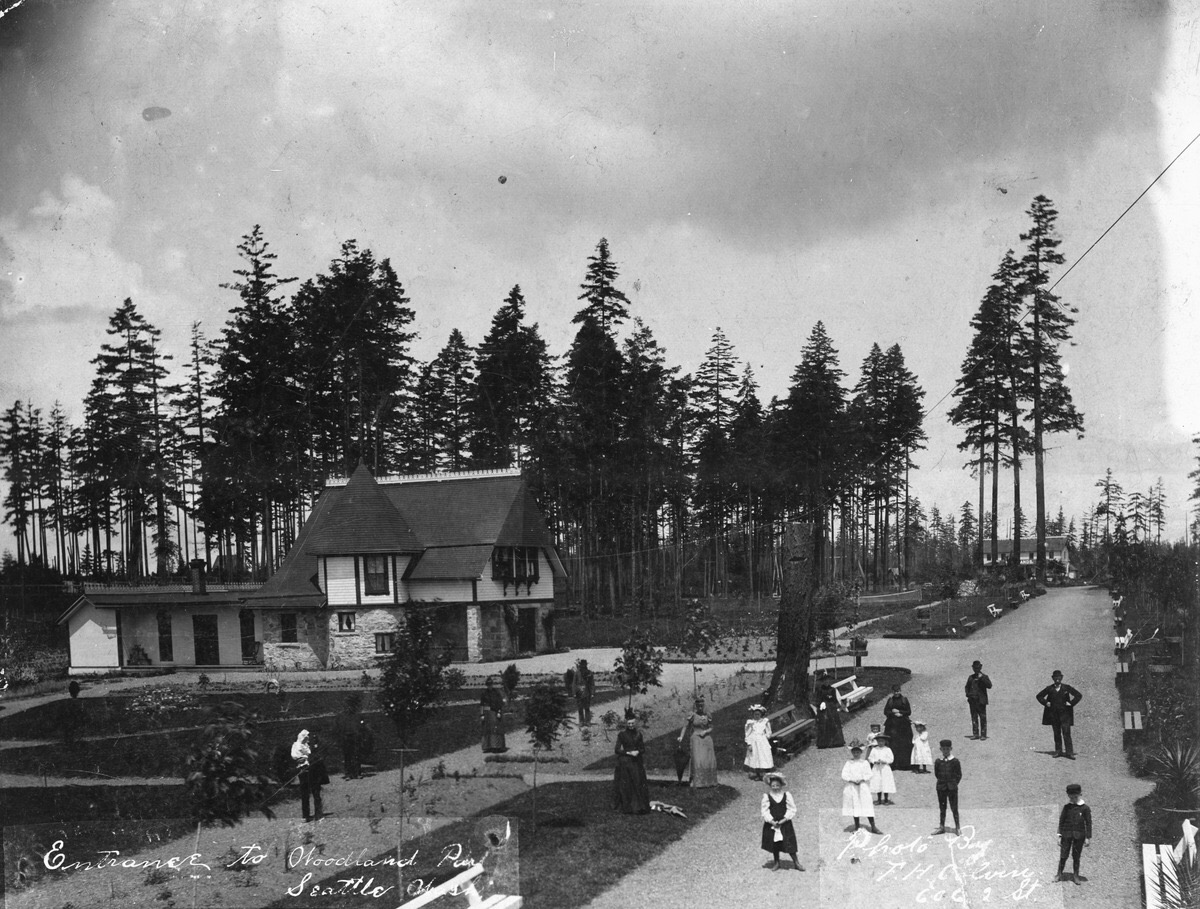 1891 photo showing the lodge at south entrance of Woodland Park estate owned by Guy Carleton Phinney. Hotel is seen in the background and the two boys on the right side of road are Arthur and Walter, Guy Phinney's sons. (Seattle Municipal Archives)